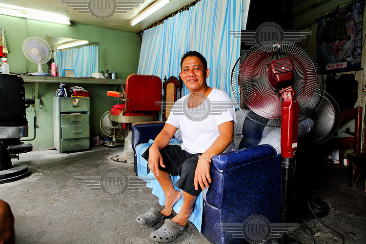 A barber sits in his shop waiting for custom.