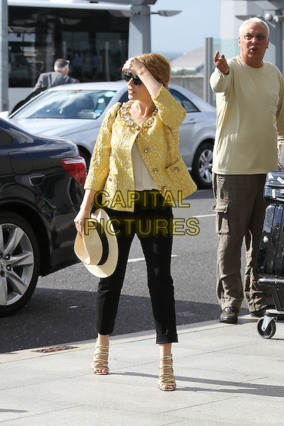 Kylie Minogue leaving  her management company and arriving at Heathrow Airport, London, England..August 2nd, 2012.full length yellow jacket gold embellished jewel encrusted collar black trousers sunglasses shades sandals beige hat hand arm.CAP/HIL.©John Hillcoat/Capital Pictures .