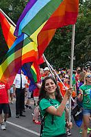 Woman waving rainbow flag, Seattle PrideFest 2015, Washington State, WA, America, USA.