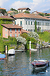 Colorful houses and a beautiful boat on the lake town of Sala Comacina on Lake Como, Italy.