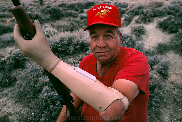 Bill Haeck of Rock Springs, Wyoming is an avid hunter who relies on his artificial myoelectric arm to continue his hobby after losing his arm in an accident.  Researchers at the University of Utah gave him a myoelectric arm, which he controls by flexing the muscles in his arm that are still intact. Sensors on the inside of the prosthetic arm socket pick up the faint electrical signals from the muscles and amplify them to control the robot arm. In this way, Haeck can do most things as he did before his accident but he often forgets to charge the battery. Seen here target shooting behind his house.