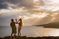 Couple on cliff giving high five overlooking bay in Lanai, Hawaii