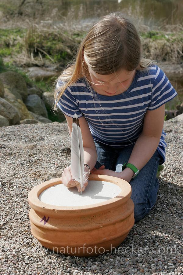 Kinder bauen eine Sonnenuhr, in einen mit Sand befüllten Blumentopf wird eine Feder gesteckt, deren Schatten die Uhrzeit zeigen soll