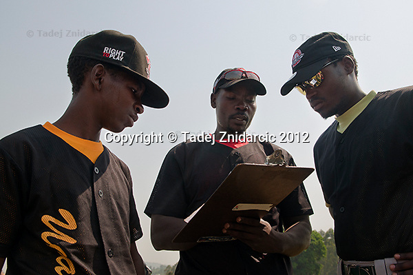 Ugandan baseball player Ivan Matovu (L), head coach George Mukhobe (middle) and Aron Kirya (little league coach) before the game in Mpigi, Uganda on January 17 2012 between Ugandan Little League team and Canadian Little League team from Langley.