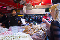 London, UK. 25.10.2014. A man serving a customer on a sweets and pastries stall on Borough Market, Southwark. Photograph © Jane Hobson.