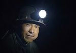 A miner inside a mine in Potosi, Bolivia. The mine produces silver and other metals. The man is chewing coca leaves, thus the lump in his cheek.