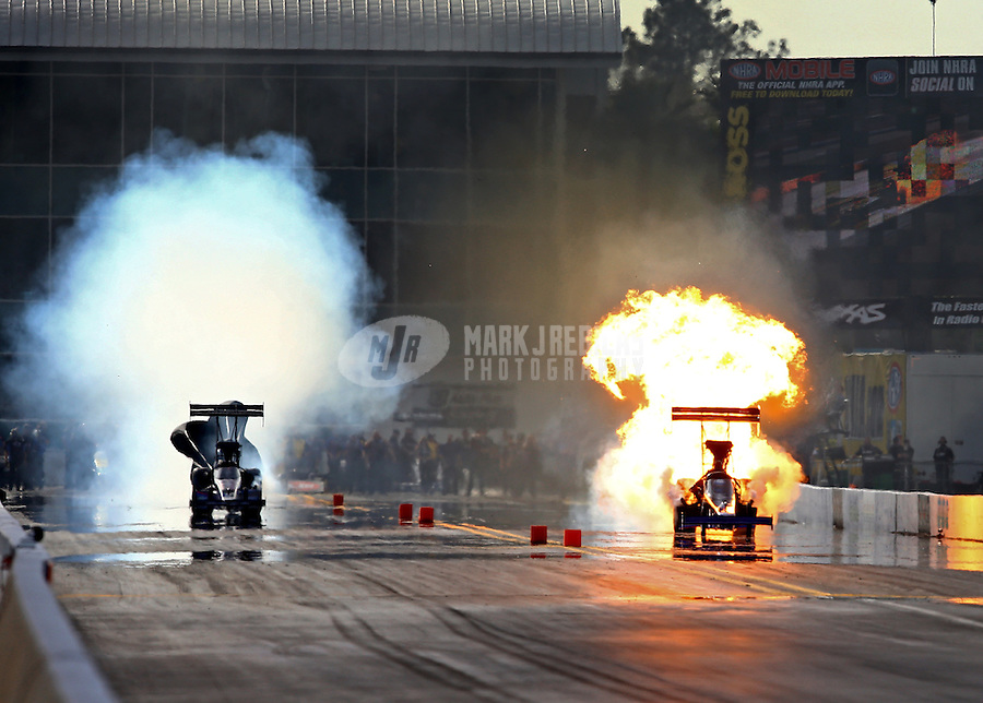 Mar 15, 2014; Gainesville, FL, USA; NHRA top fuel dragster driver Pat Dakin (right) explodes an engine alongside J.R. Todd during qualifying for the Gatornationals at Gainesville Raceway Mandatory Credit: Mark J. Rebilas-USA TODAY Sports