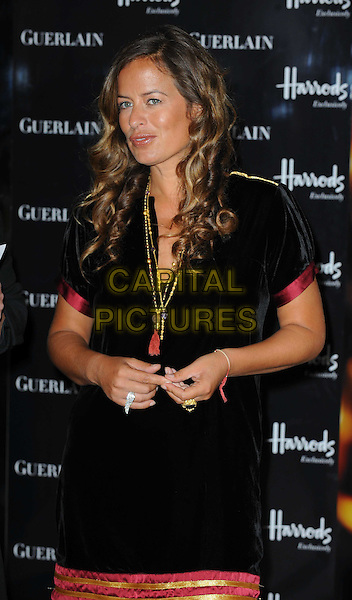 JADE JAGGER.Launches her Shamilar Eau De Parfum bottle at Harrods, Knightsbridge, London, England, UK, .September 8th, 2010..photocall half length black gold necklace tassel  red trim trimmed velvet dress rings .CAP/WIZ.© Wizard/Capital Pictures.