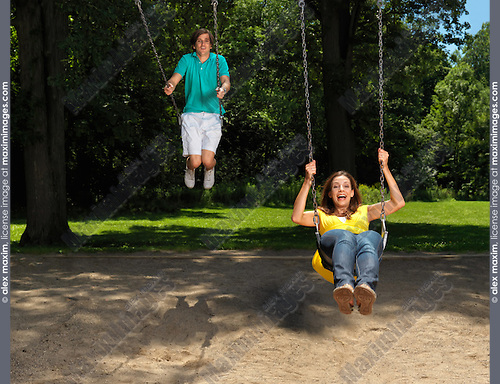 Young couple in their thirties having fun on a swing at children's playground