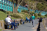 Pictured: People enjoy the sunshine at Langland Bay near Swansea, Wales, UK. Sunday 22 March 2020<br /> Re: Covid-19 Coronavirus pandemic, UK.