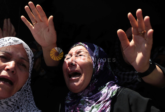 Palestinian relatives mourn during the funeral of members of Hamad family in the town of Beit Hanoun in the northern Gaza Strip July 9, 2014. Militants in Gaza fired more rockets at Tel Aviv on Wednesday, targeting Israel's heartland after Israeli attacks in the enclave that Palestinian officials said have killed at least 27 people. Israel assassinated a senior local leader of the Islamic Jihad militant group in the northern Gaza Strip early on Wednesday, neighbours and hospital officials said, and five others including family members were killed. An Israeli military spokeswoman said she had no initial details on the strike.The militant, Hafez Hamad, two brothers and his parents were killed when his house was bombed in an air strike in the town of Beit Hanoun in the northern Gaza Strip, Hamas media and Gaza interior ministry said. An unidentified woman in the house was also killed. Photo by Ashraf Amra