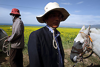 Local Tibetan men and a horse near Qinghai Lake. Qinghai Lake is China's largest inland body of water, lying at over 3000m on the Qinghai-Tibetan Plateau. The lake has been shrinking in recent decades, as a result of increased water-usage for local agriculture. Qinghai Province. China. 2010