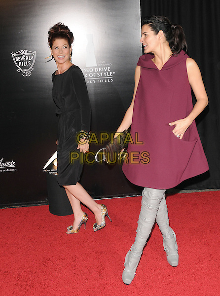 DEBRA MESSING & ANGIE HARMON.The 2009 Rodeo Walk of Style Awards held at Rodeo Dr. in Beverly Hills, California, USA..October 22nd, 2009.full length black dress  gold jewel encrusted embellished cuffs bracelets purple aubergine dress grey gray knee high thigh boots sleeveless black clutch bag profile .CAP/RKE/DVS.©DVS/RockinExposures/Capital Pictures.