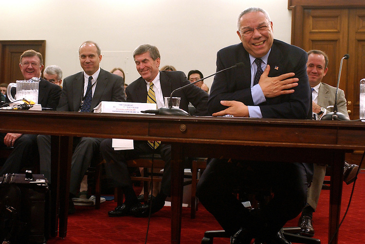 Secretary of State Colin Powell, shares a laugh with members of his staff during the House Appropriations Committee hearing on the State Department budget for FY2005.