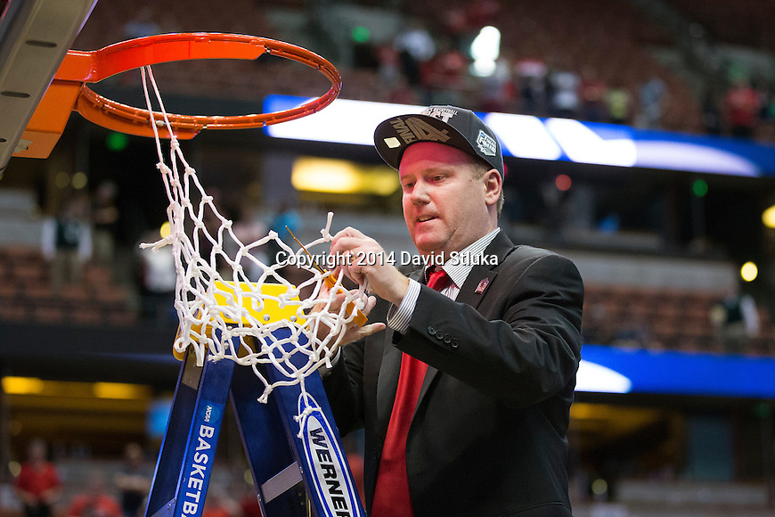 Wisconsin Badgers Associate Head Coach Greg Gard cuts down a piece of the net after the Western Regional Final NCAA college basketball tournament game against the Arizona Wildcats Saturday, March 29, 2014 in Anaheim, California. The Badgers won 64-63 (OT). (Photo by David Stluka)