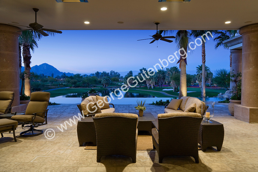 Outdoor furnishing are shown through open pocket doors with lake in background