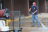 NWA Democrat-Gazette/FLIP PUTTHOFF<br /> WASH DAY<br /> Matthew Van Houden (cq), maintenance worker with Pea Ridge public schools, washes sidewalks Wednesday morning August 6 2015 at Pea Ridge High School. Activity is increasing around area schools with classes starting soon.