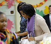 First Lady Michelle Obama and daughter Malia Obama, left, pack and give bags of food to area residents at Martha's Table on Wednesday, November 24, 2010, in Washington, DC. .Credit: Leslie E. Kossoff - Pool via CNP