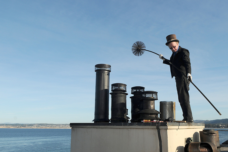 Chimney sweep Jerry Forbes works atop the roof of the Spindrift Inn on Cannery Row in Monterey, California.