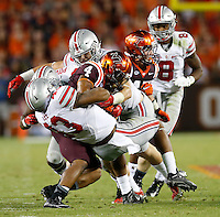 Virginia Tech Hokies running back J.C. Coleman (4) is tackled by Ohio State Buckeyes linebacker Darron Lee (43), safety Tyvis Powell (23) and defensive end Sam Hubbard (6) during Monday's NCAA Division I football game in Blacksburg, Va., on September 7, 2015. Ohio State won the game 42-24.(Dispatch Photo by Barbara J. Perenic)