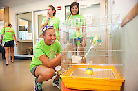 Mikayla Crieger,'19, says hello to Sparkle as she and other Salve Regina freshmen volunteer as part of their community service project.  Caroline Rodman,'19, left, and Amelia Vess,'19, in background.