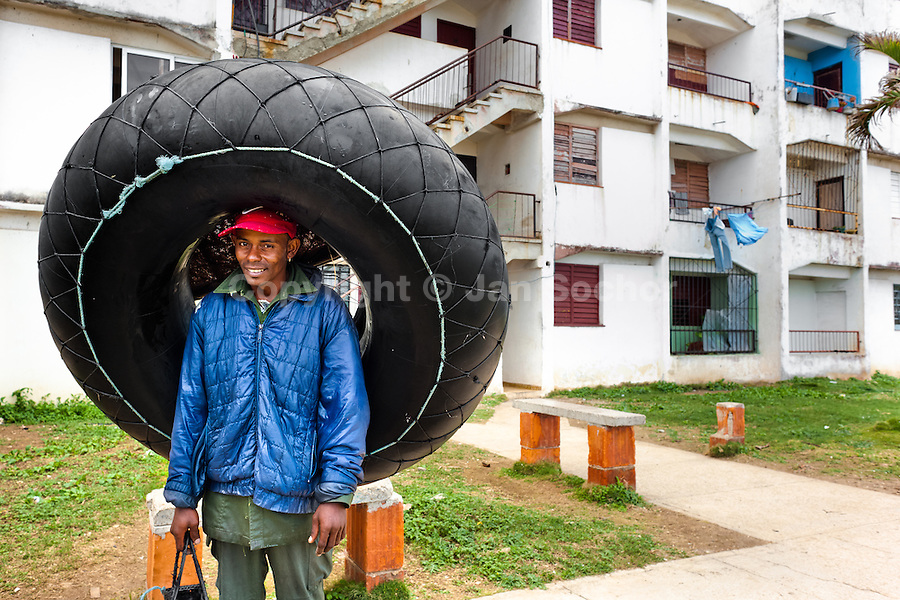 """A young Cuban man holds a tire tube, used for fishing, close to the seashore in Alamar, a public housing complex in the Eastern Havana, Cuba, 9 February 2009. The Cuban economic transformation (after the revolution in 1959) has changed the housing status in Cuba from a consumer commodity into a social right. In 1970s, to overcome the serious housing shortage, the Cuban state took over the Soviet Union concept of social housing. Using prefabricated panel factories, donated to Cuba by Soviets, huge public housing complexes have risen in the outskirts of Cuban towns. Although these mass housing settlements provided habitation to many families, they often lack infrastructure, culture, shops, services and well-maintained public spaces. Many local residents have no feeling of belonging and inspite of living on a tropical island, they claim to be """"living in Siberia""""."""