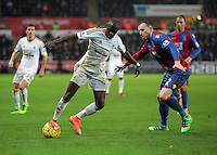 (L-R) Modou Barrow of Swansea is closely marked by Jordon Mutch of Crystal Palace during the Barclays Premier League match between Swansea City and Crystal Palace at the Liberty Stadium, Swansea on February 06 2016