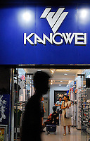 People pass Kangwei sporting goods store in Yichang city, Hubei Province, China. The casual and sporting clothes market are hot in China with major international players and also new and sophisticated Chinese brands competeting for the market place..18 May 2006