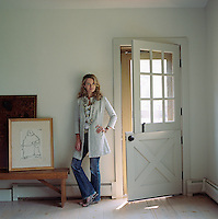 Owner and designer Edwina Hunt standing beside a stable door in the entrance of her 1770 farmhouse