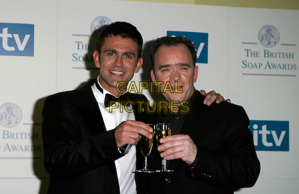 TODD CARTY & GUEST.The British Soap Awards - Pressroom, .BBC Television Centre, London, England, .May 20th 2006..half length cheers toasting glass glasses of drink champagne.REf: AH.www.capitalpictures.com.sales@capitalpictures.com.©Adam Houghton/Capital Pictures.