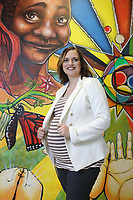 NWA Democrat-Gazette/DAVID GOTTSCHALK Madi Hutson, executive director of the Teen Action Support Center, stands in front of a mural created by students Thursday, April 5, 2018, at The Station, the new outreach center for Northwest Arkansas teens in Springdale.