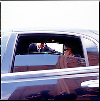 Man in suit looking through limousine window at woman inside