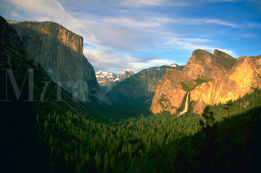 Sun shinning on forest, peaks and waterfall in Yosemite Valley, California.