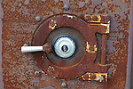 Old rusted safe door with combination lock.