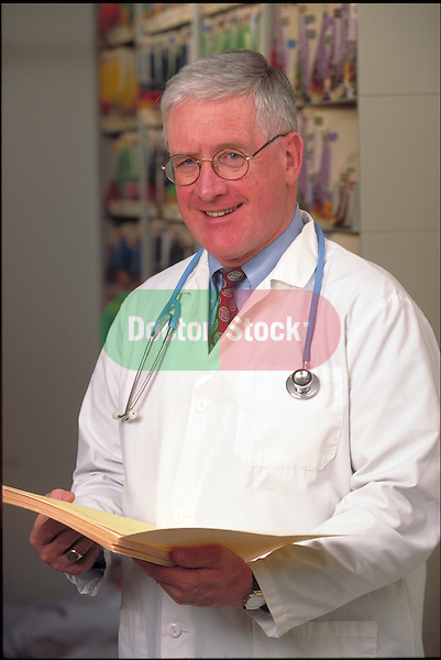 portrait of smiling doctor holding medical charts