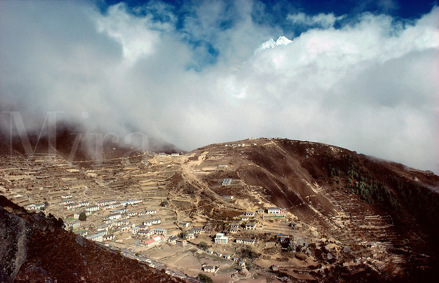 © David Paterson.The Sherpa capital, Namche Bazar, with the 6700m. peak Tamserku appearing above a layer of cloud. Khumbu region, Nepal...Keywords: Sherpa, Namche, Nauche, Bazar, Baazar, Khumbu, Nepal, Himalaya, capital, village, township, settlement, mountain, peak, summit, remote