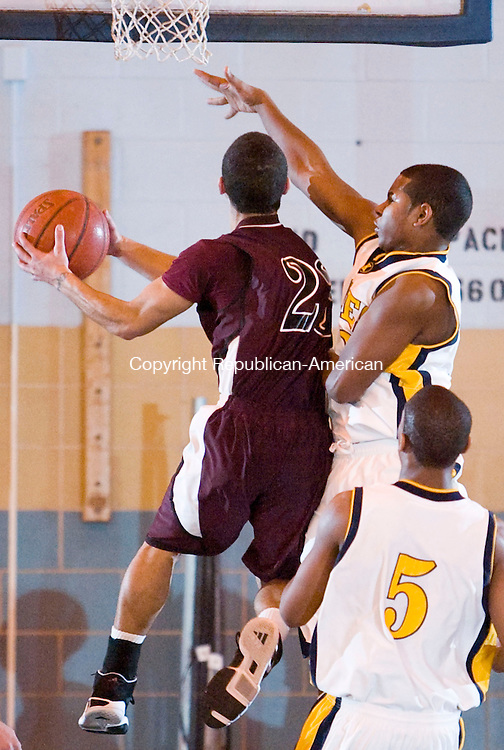 WATERBURY, CT--04 January 08--010408TJ04 - Kennedy's Donald Cardoza (33), right, tries to block a drive by Torrington's Andre French (23) during Torrington High School's 43-40 victory over John F. Kennedy High School on Friday, January 4, 2008. T.J. Kirkpatrick/Republican-American