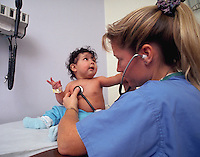A nurse examines a toddler in a doctor's office.