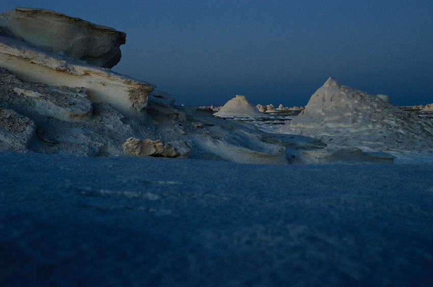 Weird rock formations sprout from the White Desert at dusk