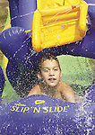 Nine-year-old Derek Leal of Holland splashes along on a water slide in his front yard to get some relief from local high temperatures on Thursday afternoon..(7/18/02)