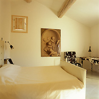 This white bedroom is decorated with a trompe l'oeil grisaille painting and a chair and desk covered in cowhide