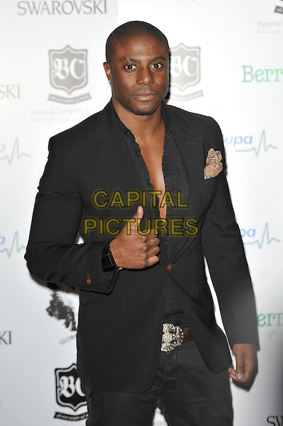 Leo Ihenacho.'Global Angels Awards', The Park Plaza Hotel, Westminster, London, England. 2nd December 2011..half length black jacket shirt undone chest thumb up gesture .CAP/MAR.© Martin Harris/Capital Pictures.