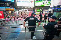 "NYPD Counterterrorism officers guard the yoga practitioners in Times Square in New York as they practice yoga on the first day of summer, Monday, June 20, 2016. The 14th annual Solstice in Times Square, ""Mind Over Madness"",   stretches the yogis'  ability to block out the noise and the visual clutter that surround them in the Crossroads of the World. (© Richard B. Levine)"