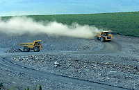 Billowing dust follows a dump truck in a quarry.
