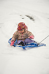 Toddler being pulled on sled in snow.