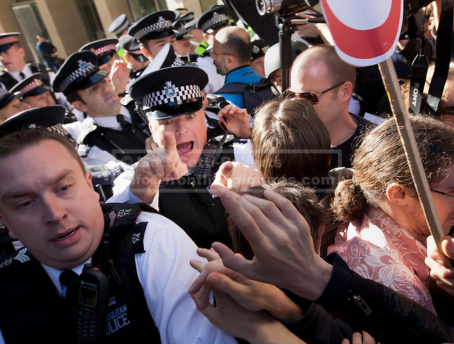 15/10/2011. LONDON, UK. Police scuffle with Occupy London protesters at an entrance to Paternoster Square during the Occupy London protest. As part of an anti-capitalist protest taking place in cities across the globe, demonstrators attempt to occupy Paternoster Square in London under the name Occupy London Stock Exchange.  After being refused entry to the square itself thousands of protesters occupied the area outside St Paul's Cathedral with some erecting tents. Credit should read: Matt Cetti-Roberts