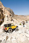 A yellow Jeep with the Motherlode Rock Crawlers crawls over a pile of rocks on a road leaving the Argus Range, Calif.