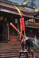 A burning red candle sets on top of an iron elephant candle-holder in front a Chinese Buddhist temple.