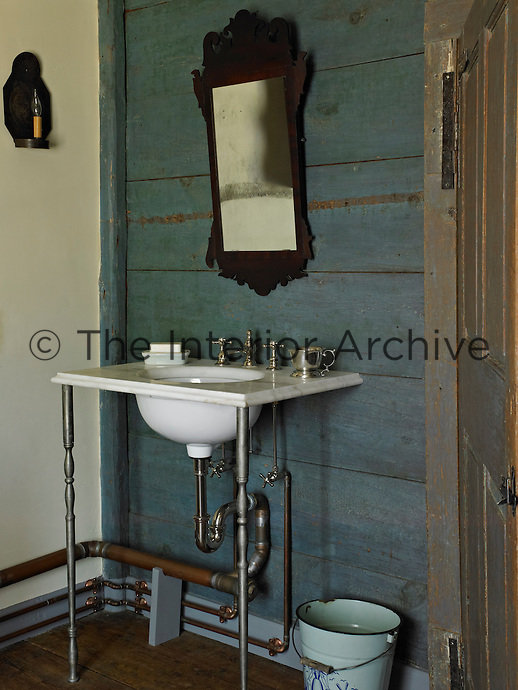 A Chippendale mahogany mirror hangs above the wash basin in the wood-panelled bathroom