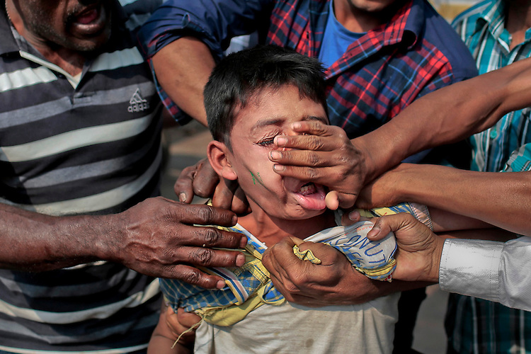 A mob in Bangladesh's capital thrashes 12-years-old Manik on suspicion that he explodes a homemade bomb at a park in Dhaka, Bangladesh, Saturday, Feb. 14, 2015. He is one of three children believed to have exploded a homemade bomb at a park where people throng to celebrate the Valentine's Day during the ongoing nationwide blockade called by the opposition Bangladesh Nationalist Party (BNP) led alliance. The children claim they picked up the device while playing there. (A.M. Ahad)